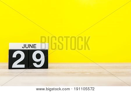 June 29th. Day 29 of month, calendar on yellow background. Summer day. Empty space for text.