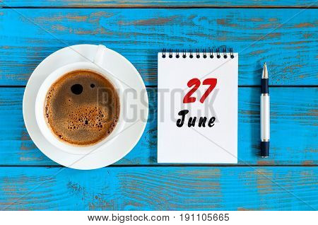 June 27th. Image of june 27 , daily calendar on blue background with morning coffee cup. Summer day, Top view.