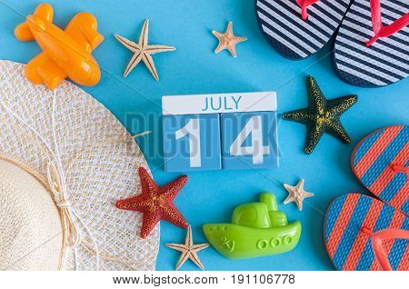 July 14th. Image of july 14 calendar with summer beach accessories and traveler outfit on background. Summer day, Vacation concept.