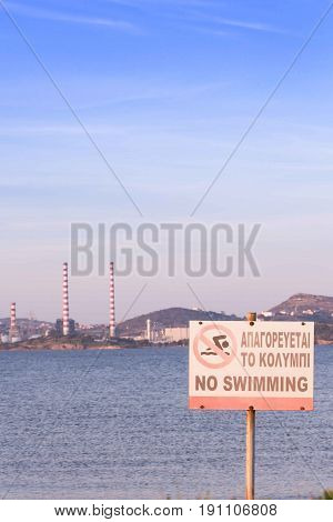 No Swimming Sign By The Beach,in Greek And English, With Power Plant Station In The Background.