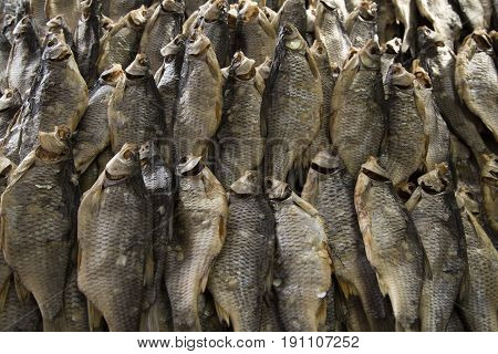 Dried fish on the table. Salty dry river fish as background top view.
