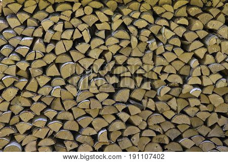 Pile firewood prepared for fireplace. Kiln-dried firewood background. Wall of dry chopped firewood prepared for winter. Natural old woodpile - fuel for boiler.