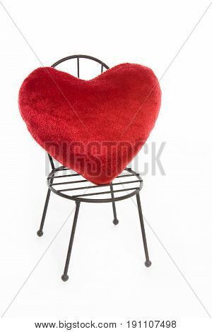 A small red heart placed on a chair. On white background