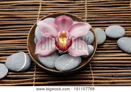 Set of gray stones with pink orchid in bowl on mat