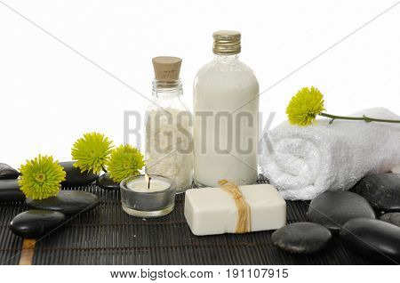 Spa setting with candle, towel ,green gerbera ,flower ,soap ,salt in bottle, on mat