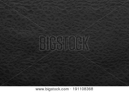 background or wallpaper with abstract texture of fabric or cotton material of black color and spotty sites of a grid