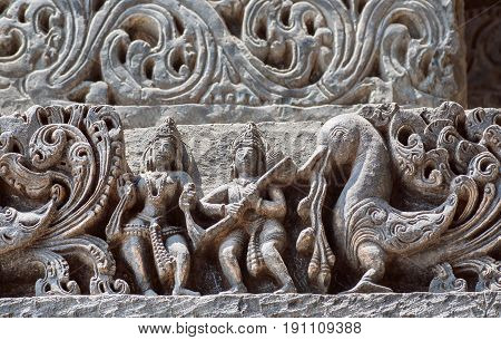 Background in Indian raditional style with reliefs and fantasy bird and ancient people. Interior of the 12th century Hoysaleshwara temple in Halebidu, Karnataka state, India
