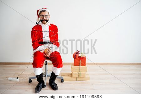A portrait of a Santa Claus tied to a chair