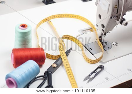 Work place of seamstress, tools on white table