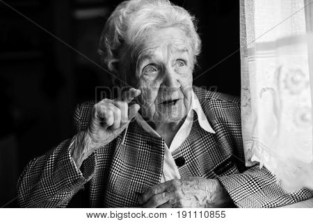 Portrait of an elderly women emotionally. Black-and-white photo.