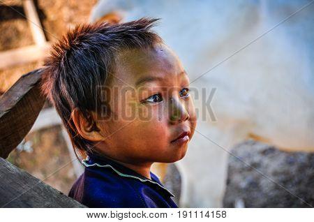 CHIANG MAI, THAILAND - DECEMBER 21, 2012: Thai boy in a village near Chiang Mai in Northern Thailand