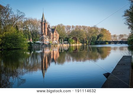 Minnewater Castle and lake panorama in Bruges Belgium