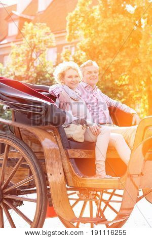 Smiling middle-aged couple sitting in horse cart on city street
