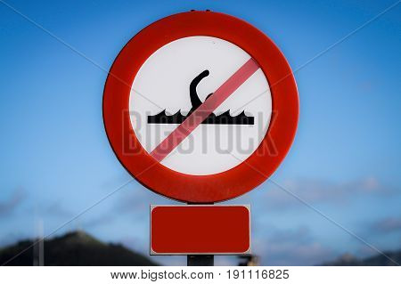 Banned bathing sign in the harbor in blue sky