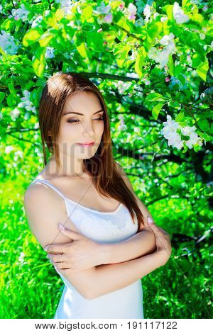 beautiful young woman with the apple tree in summer time