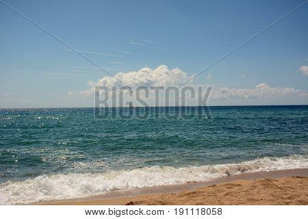 Turquoise deep sea, sailboat on the horizon, sandy beach, clouds. Badalona beach