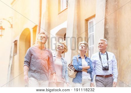 Smiling friends looking up while walking by building
