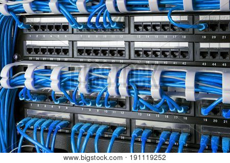 Network panel, switch and internet cables in data center. Network switch and blue ethernet cables, Data Center Concept.