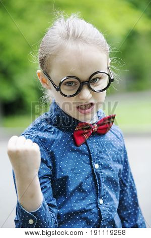 young blond boy with bow tie and big glasses showing his fist