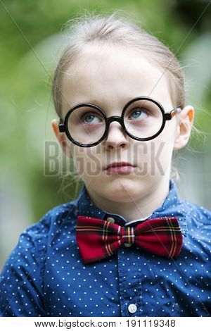 portrait of young blond boy with bow tie and big glasses