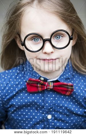 blond boy with bow tie and big glasses smiling at camera