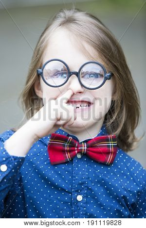 funny portrait of boy with bow tie and big glasses picking his nose