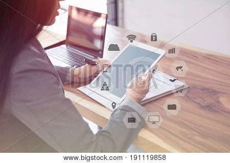 asian businesswoman using a digital tablet in office. young female entrepreneur chatting on touch pad with communication and internet icon while sitting in cafe coffee shop
