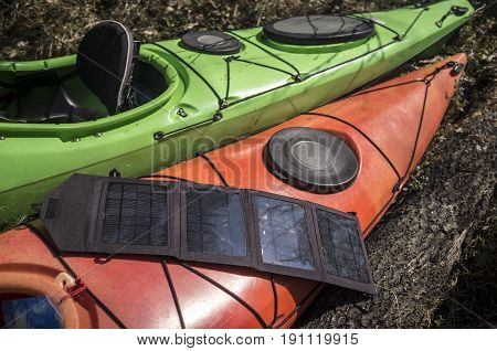 Portable solar panels lie on an orange kayak and accumulate energy.