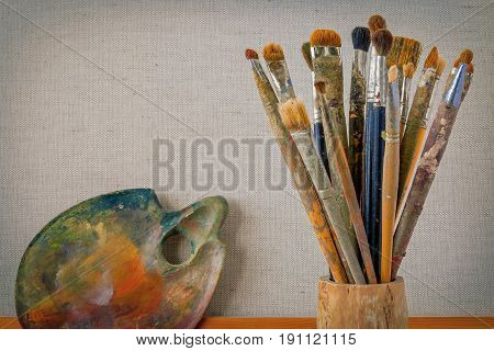 The wooden palette and brush artisans stand on the background of a stretcher with a stretched canvas