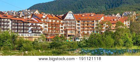 Bansko, Bulgaria - June 13, 2017: St. Ivan Rilski hotel and green pine trees mountains panoramic banner in bulgarian ski resort Bansko