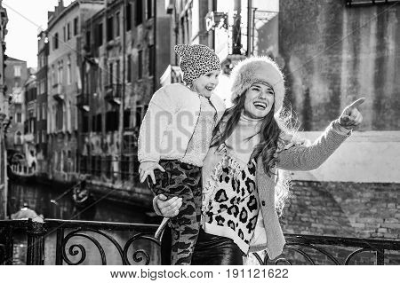 Mother And Daughter Travellers In Venice Pointing At Something