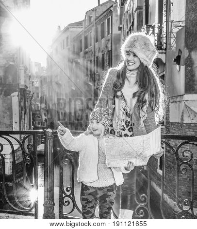 Venice. Off the Beaten Path. Full length portrait of happy young mother and child tourists in Venice Italy in the winter with map