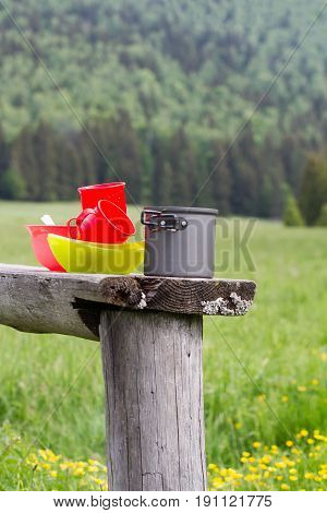 vertical front view of camping food preparing freshly washed bowls and pots on a wooden bench with green field and forest in the background copyspace