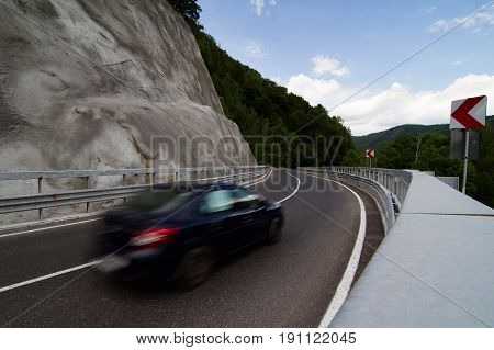 horizontal rear view of a black car with motion blur on a steep asphalt mountain road curve