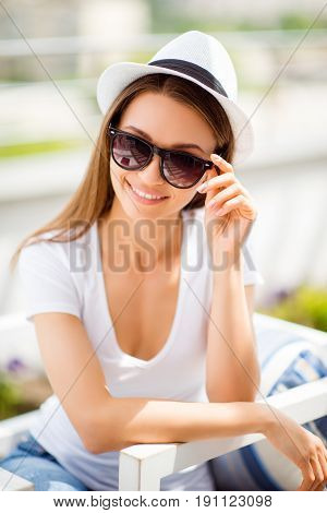Summer Mood! Happy Young Girl On Vacation In An Open Air Light Cafe. She Is In A Stylish Hat, Sungla