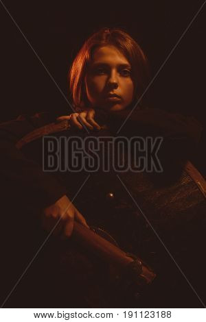 Pretty sad scandinavian girl posing with shield and axe over dark background