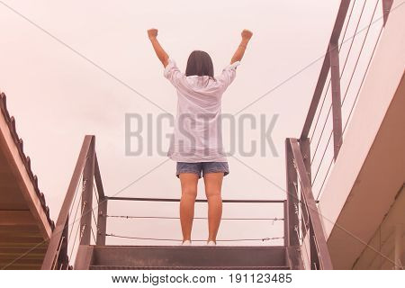 Business Success Concept : Asian woman standing on top of stair and raise up her hands. 9autumn filter effect)