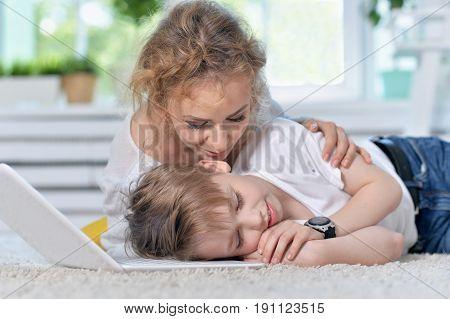 Mother awaken little son who sleeping on floor near laptop
