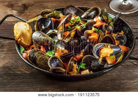A closeup of a skillet of marinara mussels on a dark rustic background with a piece of bread, and a glass of wine