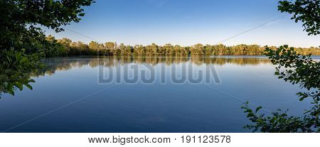 French countryside - Lorraine. Panorama of a small lake with trees in the background.