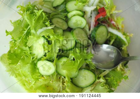 fresh vegetable salad with tomato cucumber and salad frisee in a bowl. Process of cooking. Close up selective focus.