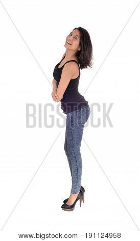 A beautiful young Hispanic woman standing in profile in a black t-shirt and jeans looking into the camera isolated for white background.