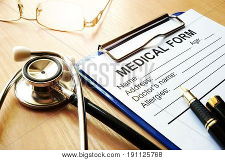 Stethoscope and medical form on a worktable.