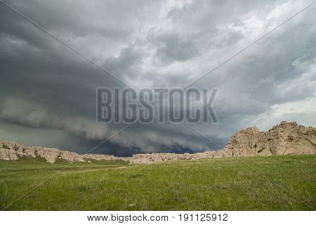 A low and ominous shelf cloud approaches rocky bluffs on a hillside in Nebraska.