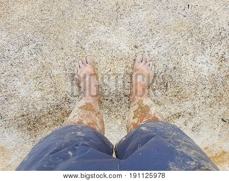 bare muddy feet through the legs on the concrete ground