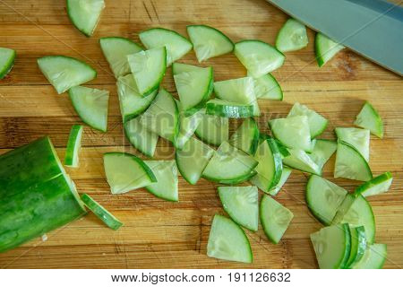 Pieces of cucumber for salad on a wooden cutting board and cook knife