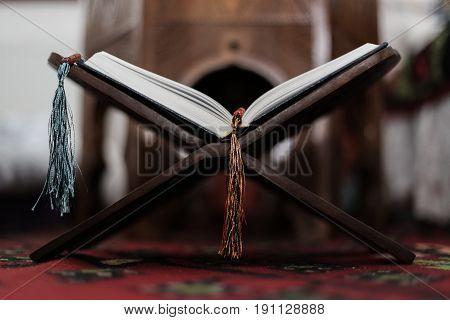 Quran-holy Book Of Muslims, An Open Book On A Stand With Rosary