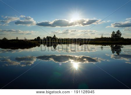 Summer landscape river and clouds reflected in water, sunset