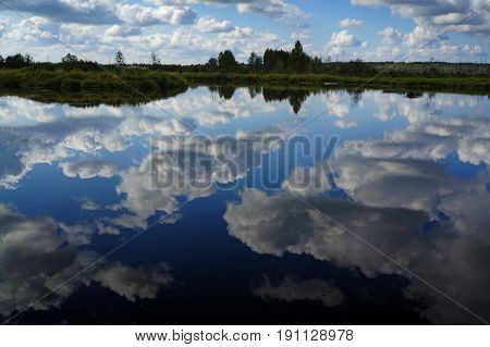 Summer landscape river and clouds, reflected in water