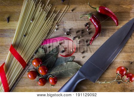 Pasta background. Dry pasta with hot pepper, tomatoes, onion, garlic. On a black wooden background. Pasta ingredients. Cherry-tomatoes